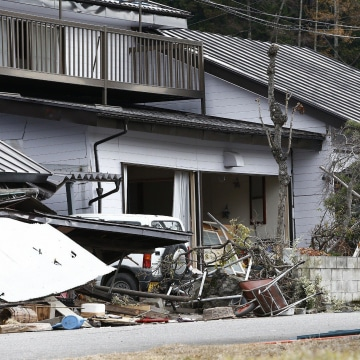 Image: Local residents look at a collapsed house after a strong earthquake hit the area the night before, in Hakuba