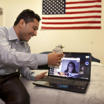 Image: Former interpreter Mohammed Usafi talks to his sister back in Afghanistan from his new home in the US