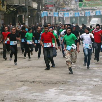 Image: Participants compete in a running race along a street in Aleppo's Bustan al-Qasr neighbourhood