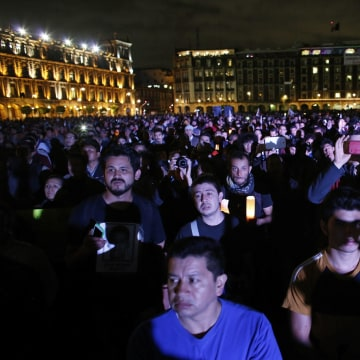 Image: Demonstrators listen to a speech delivered by the father of one of the 43 missing students of the Ayotzinapa teachers' training college, during a protest at Zocalo square in Mexico City
