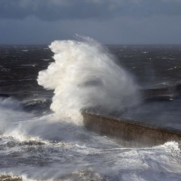 Image: Large waves crash over the harbor wall in the town of Whitehaven in Cumbia