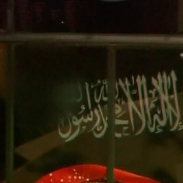Image: Video grab shows a black flag with white Arabic writing held up at the window of the Lindt cafe, where hostages are being held