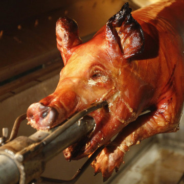 "Image: A pig by Chef's Paella chef, Jorge Suarez, also known as ""Chino"" Chef Paella, who specializes in slow cooked pork, slow cooks in Paella's portable cooker at the customer's home in Miami, Florida"