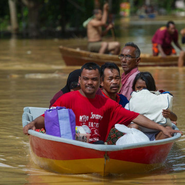 Image: A family ride on a boat through floodwater in Pengkalan Chepa