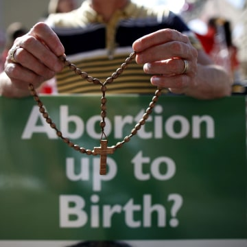 Image: A protester holding rosary beads with an anti-abortion placard in front of the gates of the Irish Parliament