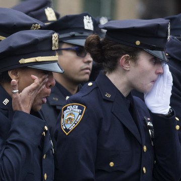 Image: Police officers wipe their tears during the funeral of New York Police Department Officer Wenjian Liu