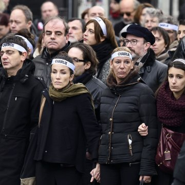 "Image: Cartoonist Corinne Rey (3rd left in green scarf) known as Coco, a survivor of the attack on the Charlie Hebdo satirical magazine, and other staff members, link arms as the take part in a Unity rally ""Marche Republicaine"" on January 11, 2015 in Pari"