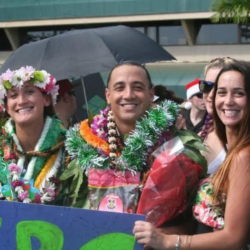 Kalā Kaawa -- covered in lei from friends, family, and complete strangers -- poses with friends after the University of Hawaii graduation ceremony.