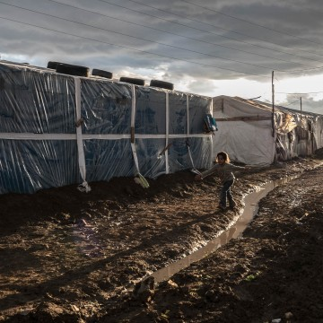 Syrian refugee children play in the mud, Bekaa Valley, Lebanon.