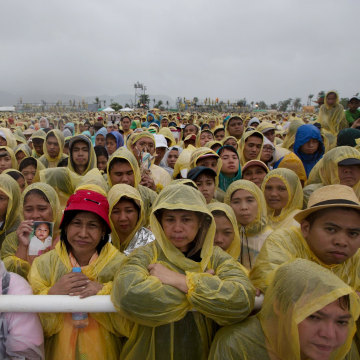 Image: People listen to Pope Francis giving a mass in Tacloban