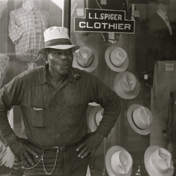African American Resident of Plain City, Ohio smoking a pipe outside of a clothing store