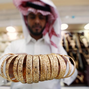 Image: A Saudi jeweller shows a customer gold bangles in a jewellery shop in Riyadh