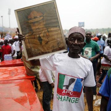 Image: A supporter holds a framed portrait of Muhammadu Buhari