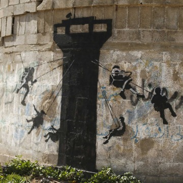 Image: A mural, presumably painted by British street artist Banksy, is seen on a wall in Biet Hanoun