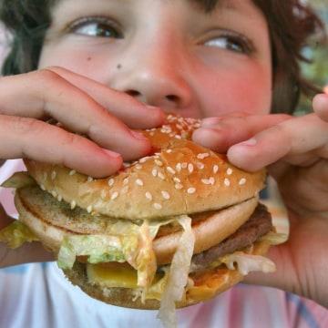 Photo: A boy eats a hamburger.