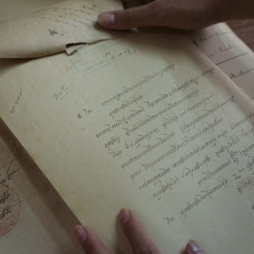 Image:  Cheryl Yin studies an old document in the National Archive of Phnom Penh