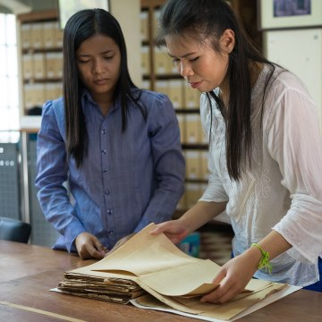 Image:  Cheryl Yin studies an old document in the National Archive of Phnom Penh.