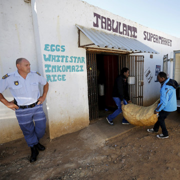 Image: Police officer looks on as a foreign nationals clear items from their shop for fear of attacks in Primrose outside Johannesburg