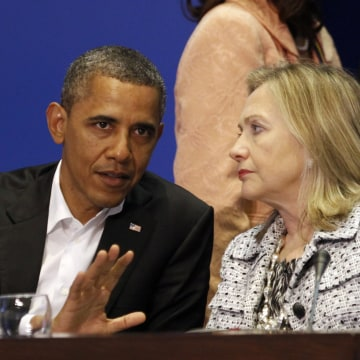 Image: U.S. President Barack Obama and Secretary of State Hillary Clinton talk during the plenary session of the Summit of the Americas in Cartagena