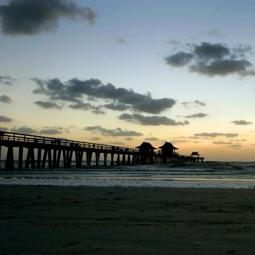 Image: A man runs along the beach near Naples Pier