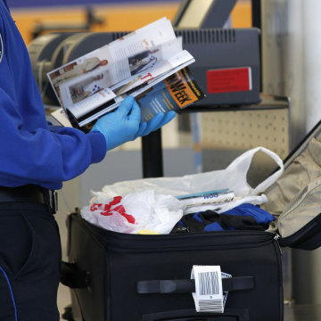 Image: A TSA officer inspects items from a piece of luggage at Los Angeles International Airport in Los Angeles