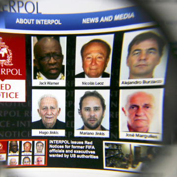 Image: The homepage of the Interpol website is seen through a magnifying glass in this picture illustration taken in Berlin