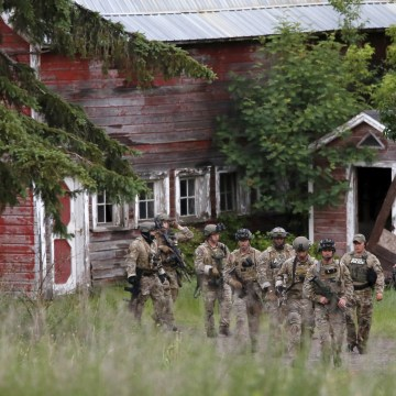 Image: Police officers search a property near the Clinton Correctional Facility in Dannemora