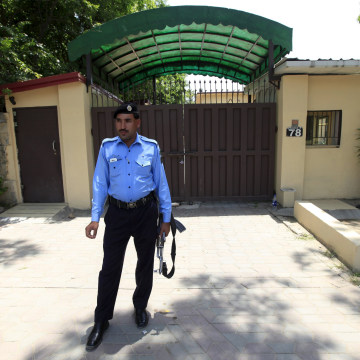 Image: A police officer stands guard outside Save the Children's office in Islamabad