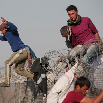 Image: Syrian refugees jump over the border fence from Syria to Turkey