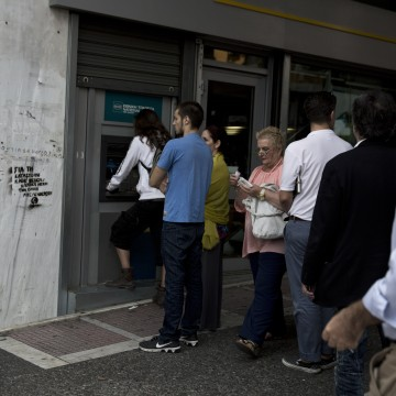 Image: People line up at an ATM outside a branch of the National Bank, in central Athens, on Friday.