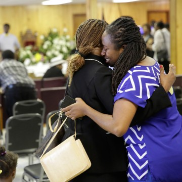 Image: Waltrina Middleton, right, cousin of shooting victim DePayne Doctor, embraces Claudia Lawton