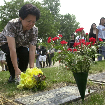 Amy Lee places flowers at the grave stone of her nephew, Vincent Chin.