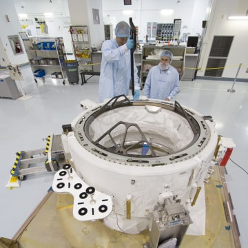 Image: Engineers check measurements on the International Docking Adapter