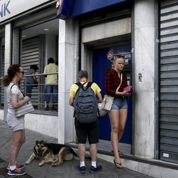 Image: People line up to withdraw cash from an ATM outside a Eurobank branch in Athens