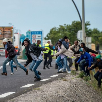 Image:Policemen try to prevent migrants from reaching the Channel Tunnel