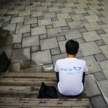 Image: Jiang Hui, whose mother was on MH370, checks news of the debris discovery