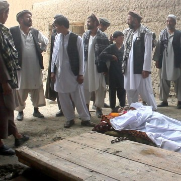 Image: Relatives stand over bodies of victims of gunfight at wedding party in Deh Salah, Afghanistan