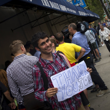 """Image: Ticket holder holds handwritten sign as he waits to enter studio for the last taping of Comedy Central's """"The Daily Show with Jon Stewart"""" in New York"""