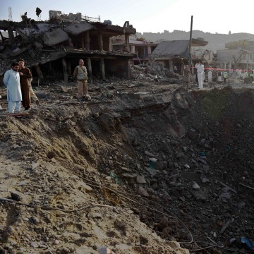 Image: Afghan security forces and residents stand near the crater from a powerful truck bomb in Kabul