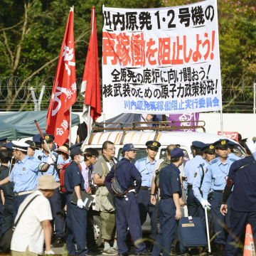 Image: Police officers stand guard as protesters stage a rally at the gate of the Sendai Nuclear Power Station