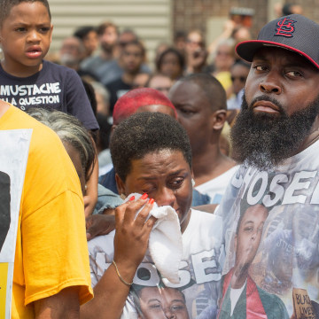 Image: Michael Brown Sr. comforts his wife Cal Brown on Sunday