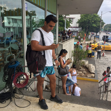 Image: In Havana, Cuba, people congregate around some new Wifi hotspots once or a few times a week.  The service is spotty and expensive.