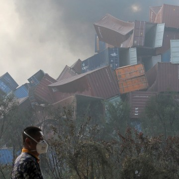 Image: A man wearing a mask walks past overturned shipping containers in Tianjin