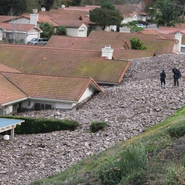 Image: A TV news crew files a report behind damaged homes after a mud slide in Camarillo Springs, California