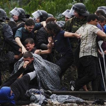 Image: Migrants fall as they make their way through police to cross Greece's border into Macedonia near Gevgelija, Macedonia