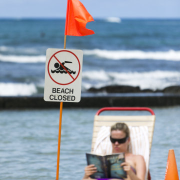 Image: A sunbather reads a book behind a beach closed sign at Waikiki Beach in Honolulu, Hawaii