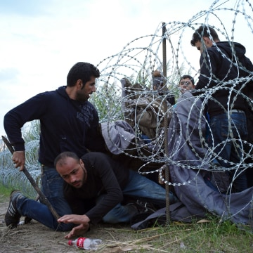 Image: Refugees cross into Hungary underneath the razor wire border fence on Wednesday.