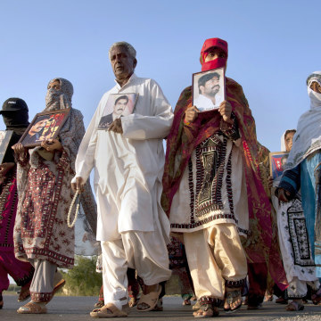 Image: Baloch families hold photographs of their relatives