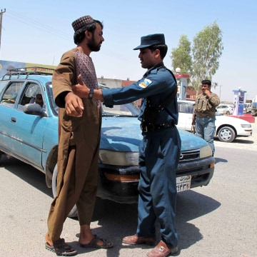 Image: An Afghan security member frisks a man at a checkpoint on a roadside in Helmand