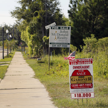 Image: For sale signs are seen on Coleman Avenue in Waveland, Mississippi